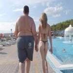 couple homme obèse- femme mince, main dans la main de dos